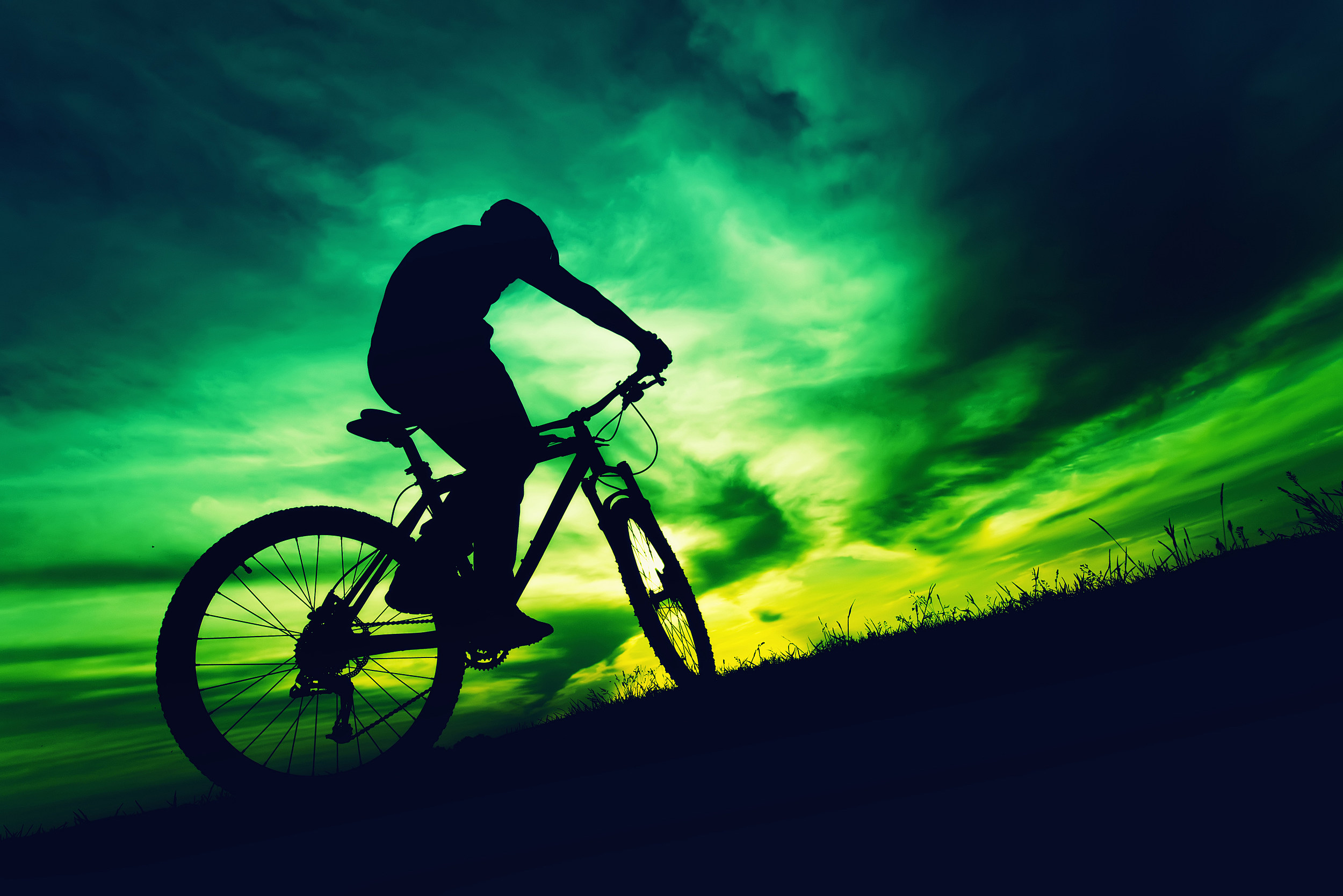 silhouette of a bicyclist against colorful sky at sundown